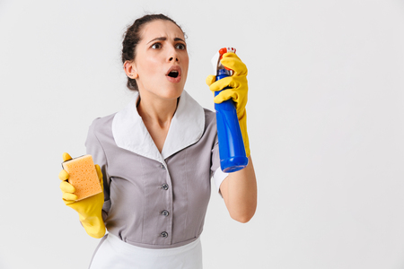 Portrait of a shocked young housemaid dressed in uniform and rubber gloves holding sponge and a sprayer isolated over white background Zdjęcie Seryjne - 106615622