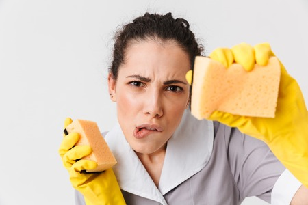 Portrait of a serious young housemaid dressed in uniform and rubber gloves holding sponges isolated over white background 写真素材