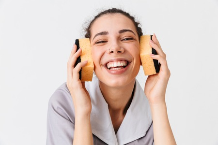 Portrait of a smiling young housemaid dressed in uniform using sponges as headphones isolated over white background