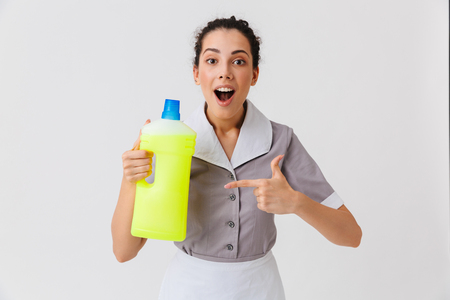 Portrait of an excited young housemaid dressed in uniform holding detergent isolated over white background Zdjęcie Seryjne - 106615661