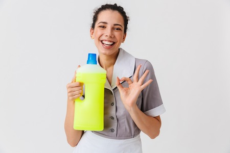 Portrait of an excited young housemaid dressed in uniform holding detergent and showing ok isolated over white background Zdjęcie Seryjne