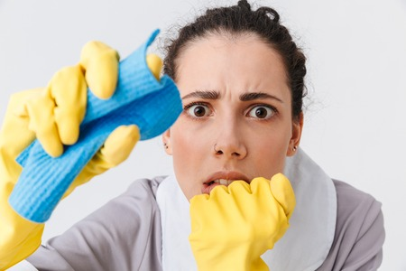 Portrait of a scared young housemaid dressed in uniform and rubber gloves using a sponge isolated over white background Stock Photo