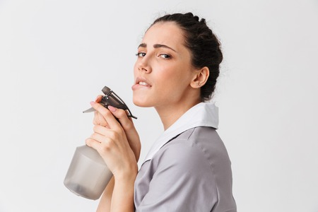 Portrait of a seductive young housemaid dressed in uniform using bottle sprayer isolated over white background Zdjęcie Seryjne - 106615706