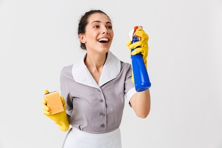 Portrait of a cheerful young housemaid dressed in uniform and rubber gloves holding sponge and a sprayer isolated over white background