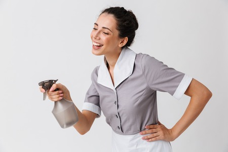 Portrait of a cheerful young housemaid dressed in uniform using bottle sprayer isolated over white background Zdjęcie Seryjne