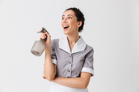 Portrait of a smiling young housemaid dressed in uniform using bottle sprayer isolated over white background Zdjęcie Seryjne