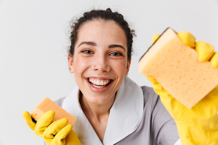 Portrait of a laughing young housemaid dressed in uniform and rubber gloves holding sponges isolated over white background Banque d'images
