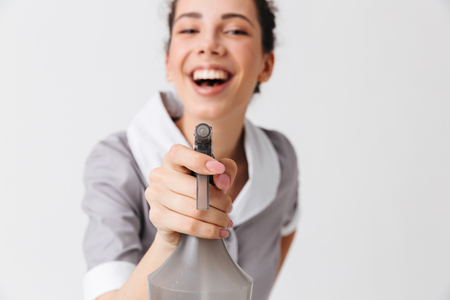 Portrait of a satisfied young housemaid dressed in uniform using bottle sprayer isolated over white background