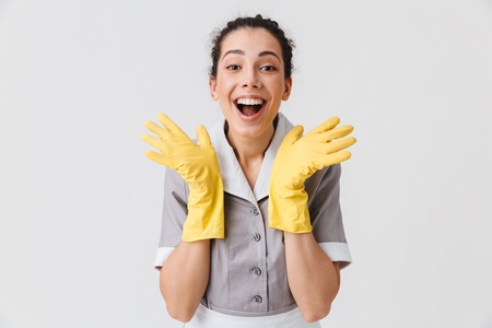 Portrait of an excited young housemaid dressed in uniform and rubber gloves looking at camera with open mouth isolated over white background