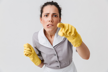Portrait of a serious young housemaid dressed in uniform and rubber gloves pointing at camera isolated over white background Stock Photo