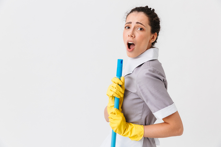 Portrait of a surprised young housemaid dressed in uniform holding a mop isolated over white background