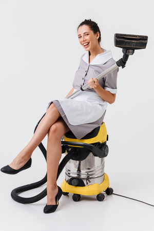Full length of a happy young housemaid dressed in uniform sitting on a vacuum cleaner isolated over white background Zdjęcie Seryjne - 106615640