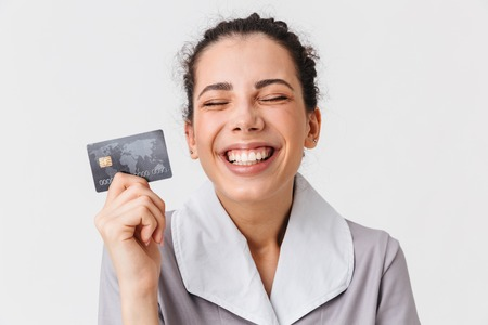 Portrait of a cheerful young housemaid dressed in uniform holding plastic credit card isolated over white background