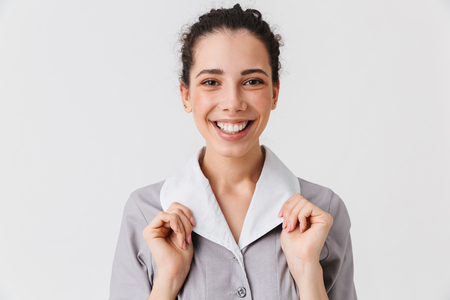 Close up portrait of a happy young housemaid dressed in uniform looking at camera isolated over white background Stock Photo