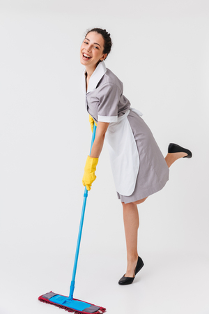 Full length portrait of a cheerful young housemaid dressed in uniform using a mop isolated over white background