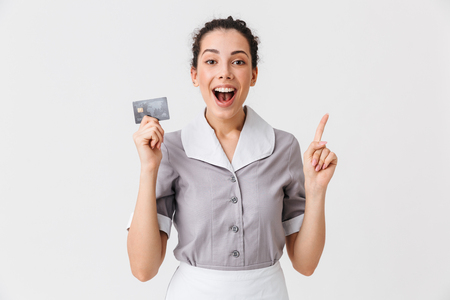 Portrait of an excited young housemaid dressed in uniform holding plastic credit card isolated over white background