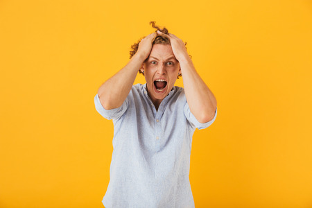 Photo of shocked young man 20s with curly hair grabbing head and shouting in anger isolated over yellow background