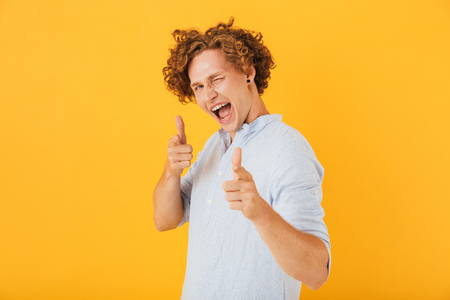 Image of european flirty guy 20s laughing and pointing finger at you isolated over yellow background