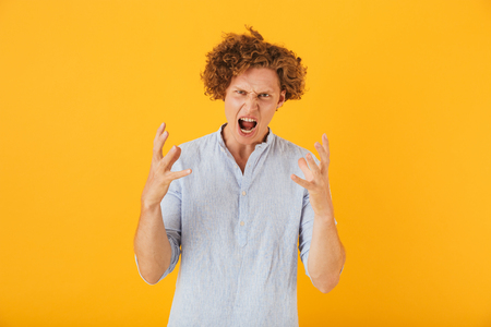 Photo of angry furious man 20s with curly hair raising hands in irritation isolated over yellow background