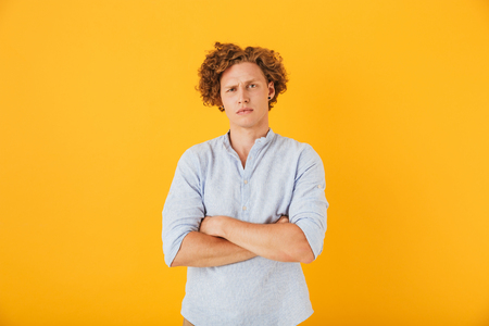Photo of upset serious man 20s with curly hair standing with arms folded isolated over yellow background