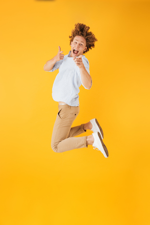 Full length portrait of beautiful curly man 20s jumping and showing thumbs up isolated over yellow background