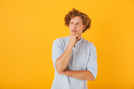 Portrait of curly young man 20s touching chin and looking aside with serious look isolated over yellow background