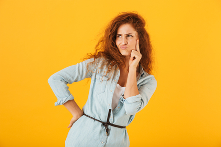 Confused displeased woman 20s thinking and looking aside isolated over yellow background Imagens
