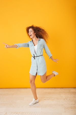 Full length portrait of surprised curly woman 20s smiling and pointing finger aside at copyspace isolated over yellow background