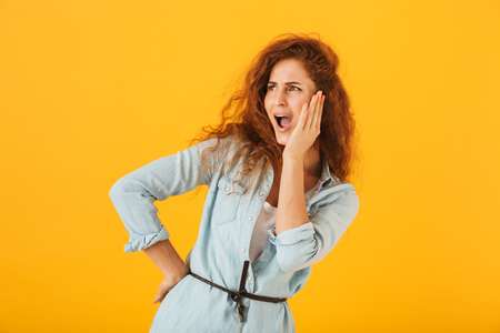 Outraged confused woman 20s grabbing face and shouting isolated over yellow background Stock Photo