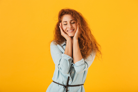 Lovely european woman 20s holding hands at face and smiling with closed eyes isolated over yellow background Archivio Fotografico - 106615269