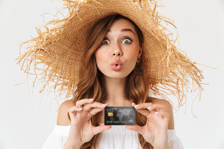 Portrait of cheerful young woman 20s wearing big straw hat rejoicing while holding credit card isolated over white background