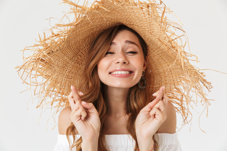 Portrait closeup of young dreaming woman 20s wearing big straw hat keeping fingers crossed and hoping for good luck isolated over white background