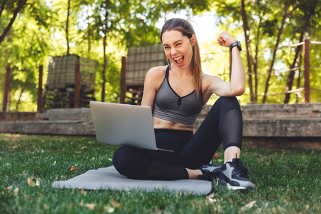 Portrait of a smiling young fitness girl using laptop computer while sitting on a mat outdoors and flexing biceps