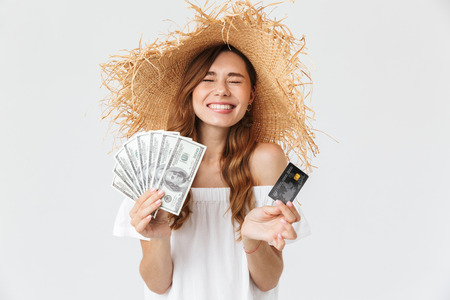 Photo of caucasian brunette woman 20s wearing big straw hat smiling while holding credit card and fan of dollar cash isolated over white background Banco de Imagens