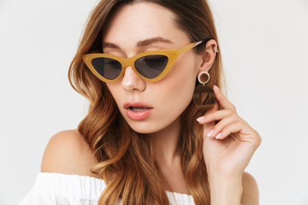 Portrait of modern fashion woman 20s wearing trendy sunglasses and earring isolated over white background