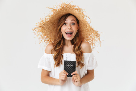 Portrait of excited summer woman 20s wearing big straw hat rejoicing while holding passport with tickets isolated over white background