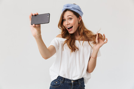 Photo of charming young woman 20s laughing while taking selfie on mobile phone isolated over white background