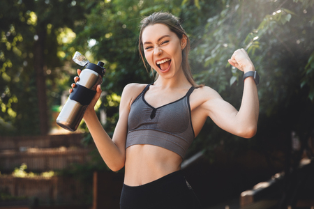 Portrait of a happy young fitness girl holding water bottle and flexing biceps outdoors Stock Photo