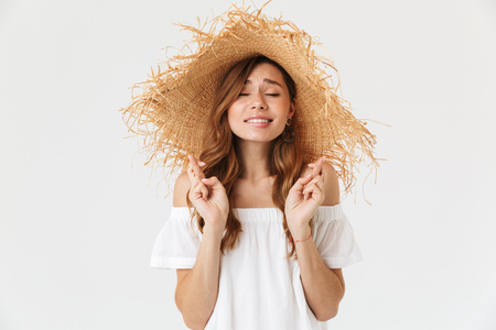 Portrait of superstitious european woman 20s wearing big straw hat keeping fingers crossed and dreaming for good luck isolated over white background Stock Photo