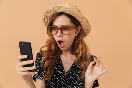 Portrait of outraged confused woman wearing straw hat and sunglasses holding and looking at mobile phone isolated over beige background