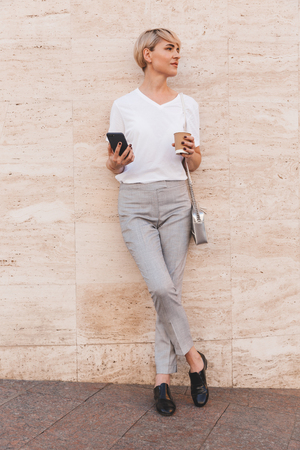 Full length image of stylish blond woman wearing white t-shirt holding smartphone while standing against beige wall outdoor in summer and looking aside at copyspace with takeaway coffee Stock Photo