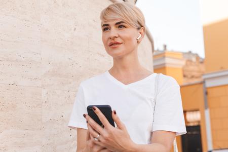 Foto der glücklichen blonden Frau, die weißes T-Shirt und Bluetooth-Kopfhörer unter Verwendung des Mobiltelefons beim Gehen in Stadtstraße trägt Standard-Bild