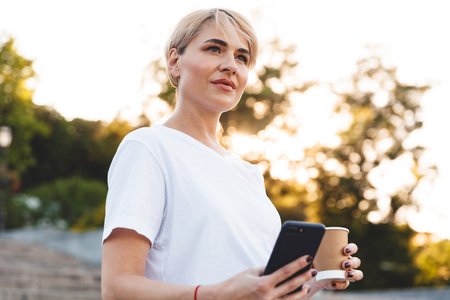 Picture of mature woman 30s with blond hair wearing casual clothing holding cell phone and paper cup with coffee while standing at city stairs
