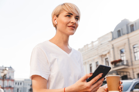 Photo of cheerful blonde woman wearing white t-shirt using cell phone and wireless earphone while sitting in summer cafe outdoor and drinking coffee from paper cup