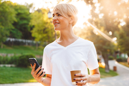 Image of beautiful happy woman with blond hair wearing casual clothing holding cell phone and takeaway coffee during walk in green park Stock Photo