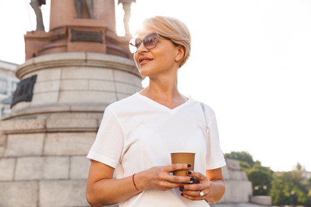 Portrait of joyful attractive woman wearing white t-shirt and sunglasses walking through city street in summer and drinking takeaway coffee from paper cup Stock Photo
