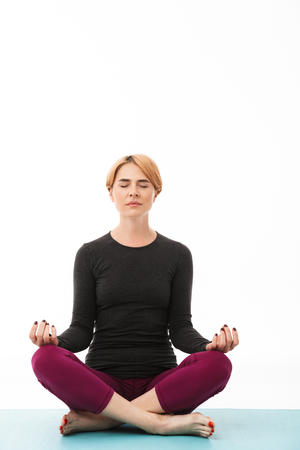 Portrait of a calm yoga woman meditating in lotus position isolated over white background Stock Photo