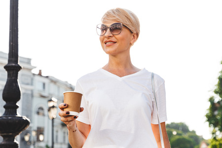 Image of happy blond woman wearing white t-shirt and sunglasses walking through city street in summer and holding takeaway coffee