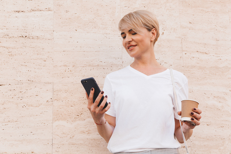 Photo of pretty blond woman wearing white t-shirt holding mobile phone while standing against beige wall outdoor in summer and drinking coffee from paper cup