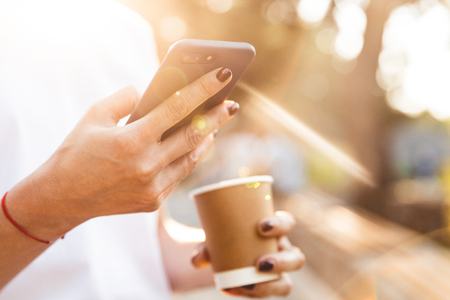 Cropped closeup image of caucasian woman wearing casual clothing holding smartphone and takeaway coffee in hands during walk outdoor